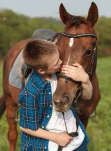 A boy kissing his horse, therapy horse research at University of Guelph.