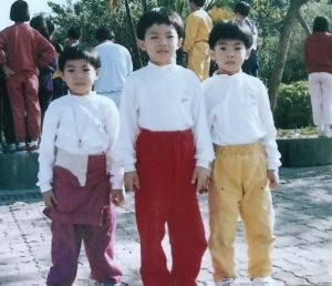 Three boys in white tops and colourful pants